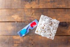 Popcorn im klassischen Kino-Umhüllungs-Kasten und in den Gläsern 3D für Wathcin Stockbild