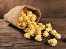Popcorn im Sackleinen und auf altem Holzfußboden stockfotografie