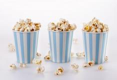 Popcorn imburrato in tazze di carta a strisce sopra fondo bianco Fotografia Stock Libera da Diritti