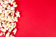 Popcorn on red background with empty space, top view. Popcorn isolated on red background. Empty space for text and design. Movie and cinema concept background Royalty Free Stock Image
