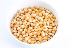 Popcorn Kernels. Unpopped in bowl on white background Stock Photo
