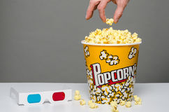 Popcorn with kernels and 3d glasses. Image of a bucket of popcorn with 3d glasses and a hand picking popcorn stock images