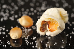 Popcorn kernels surrounded by salt grains Stock Photo