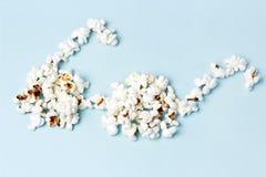 Popcorn lade ut i form av exponeringsglas på en blå bakgrundsnärbild, bästa sikt royaltyfri fotografi