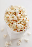 Popcorn. Lot of Popcorn in the white paper bag Royalty Free Stock Image
