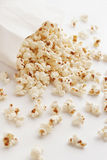 Popcorn. Lot of Popcorn in the white paper bag Royalty Free Stock Photography