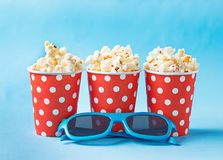 Popcorn med exponeringsglas 3d på blå bakgrund Royaltyfria Foton