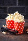 Popcorn med exponeringsglas 3d på mörk bakgrund Arkivfoton
