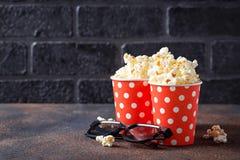 Popcorn med exponeringsglas 3d på mörk bakgrund Arkivbild