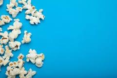 Popcorn med kopieringsutrymmet på den blåa bakgrunden royaltyfria bilder