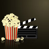 Popcorn and movie  clapper board. Popcorn and movie clapper board on dark background Stock Images