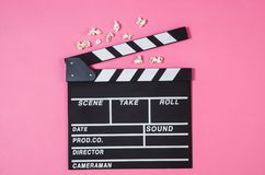 Popcorn, movie clip on pink background top view, copy space. Fresh popcorn and movie clip on pink background top view with copy space around products. Cinematic royalty free stock image
