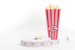 Popcorn and movie tickets. A carton of popcorn and a reel of tickets Royalty Free Stock Photos
