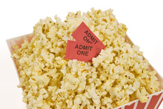 Popcorn and Movie Tickets. A container of popcorn with two movie tickets in it with a white background Stock Photos