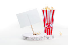 Popcorn, movie tickets and a sign. A carton of popcorn, a reel of tickets and a sign Royalty Free Stock Photos