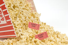 Popcorn and Movie Tickets Spilled. A container of popcorn with movie tickets in it is spilled.  White background Stock Photo