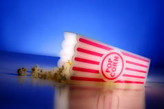 Popcorn at the Movies. Illustration of popcorn for a movie in a popcorn holder and spilling out Royalty Free Stock Photography