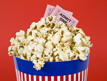 Popcorn and movies. A popcorn bucket over a red background. Movie stubs sitting over the popcorn Stock Photography