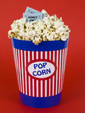 Popcorn and movies. A popcorn bucket over a red background. Movie stubs sitting over the popcorn Royalty Free Stock Images