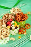 Popcorn, multicoloured drops, pretzels with salt and pistachio nuts in paper cups. On green background. Snacks assortment Royalty Free Stock Image