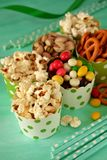 Popcorn, multicoloured drops, pretzels with salt and pistachio nuts in paper cups. On green background. Snacks assortment Royalty Free Stock Photo