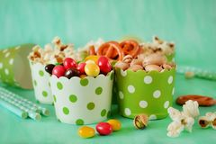 Popcorn, multicoloured drops, pretzels with salt and pistachio nuts in paper cups. On green background. Snacks assortment Stock Photos