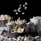 Popcorn nel moto su fondo nero Fotografia Stock
