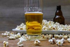 Popcorn och öl på trätabellen royaltyfri fotografi