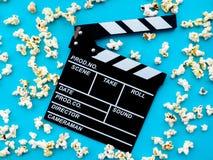 Popcorn och clapperboard på blå bakgrund begreppet av filmen, film, underhållning som annonserar royaltyfri bild