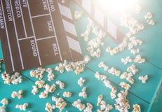 Popcorn och clapperboard på färgrik blå bakgrund arkivfoto