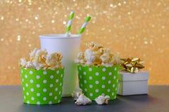 Popcorn och drink i den pappers- koppen för filmen och underhållning, en gåva, guld- bokehbakgrund royaltyfri foto