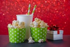 Popcorn och drink i den pappers- koppen för filmen och underhållning, en gåva, röd bokehbakgrund arkivfoto
