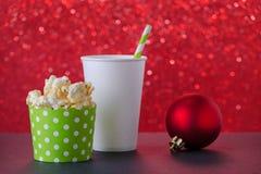Popcorn och drink i den pappers- koppen för filmen och underhållning, röd bokehbakgrund, selektiv fokus royaltyfri foto