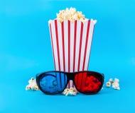 Popcorn och exponeringsglas 3D på blå bakgrund Fotografering för Bildbyråer