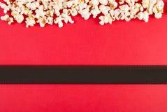 Popcorn- och filmband på röd bakgrund, bästa sikt och utrymme för text arkivbilder