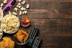 Popcorn och olika mellanmål, 3D exponeringsglas, TVfjärrkontroll på en brun träbakgrund begrepp av hållande ögonen på filmer hemm arkivfoton
