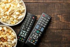 Popcorn- och TVfjärrkontroll på en brun träbakgrund begrepp av hållande ögonen på filmer hemma ovanför sikt arkivbild