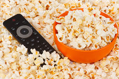 Popcorn in a orange bowl and remote control Stock Images