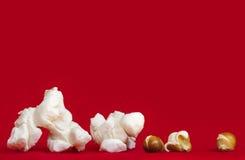 Popcorn over Trillende Rode Achtergrond Geknalde en Unpopped-Pitten Royalty-vrije Stock Afbeeldingen