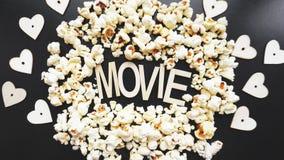 Popcorn på svart bakgrund Hålla ögonen på en film med popcorn kopiera avstånd arkivbilder