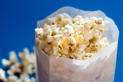 Popcorn in a paper bag. Against blue background Stock Image