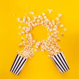 Popcorn in paper bag scattered on yellow background top view royalty free stock photos