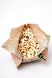 Popcorn in a paper bag on white background stock images