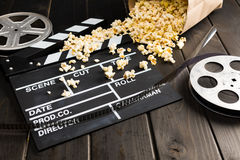 Popcorn in paper container and movie clapper board on table, Movie time concept. Close up view of popcorn in paper container and movie clapper board on table Stock Images