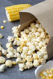 Popcorn in paper cup pouring on table.  royalty free stock image