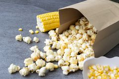 Popcorn in paper cup pouring on table.  royalty free stock photography