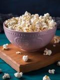 Popcorn in pink bowl on dark background Stock Photo
