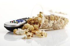 Popcorn in plastic cup alongside remote control Royalty Free Stock Image