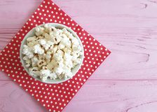 Popcorn plate natural , red napkin nutrition traditional in a polka dot pink wooden background with space for text. Popcorn plate, red napkin a polka dot pink Royalty Free Stock Photos