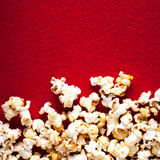 Popcorn popcorn on red textured background close up macro.  Royalty Free Stock Photography